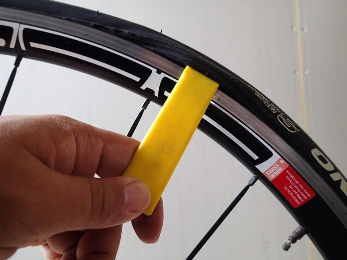 タイヤレバーを使い、タイヤの片側をリムから外す