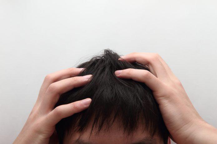 髪の毛を抑える男性