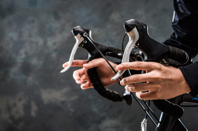 ロードバイクのハンドルを握る男性の画像