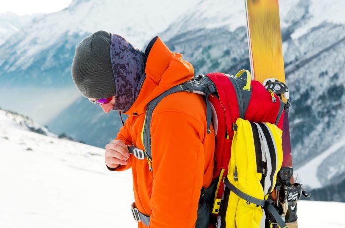 スキー用品を背負いながら雪山を歩く男性の画像