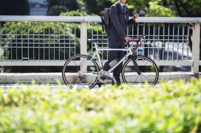 ロードバイクで通勤する男性の画像