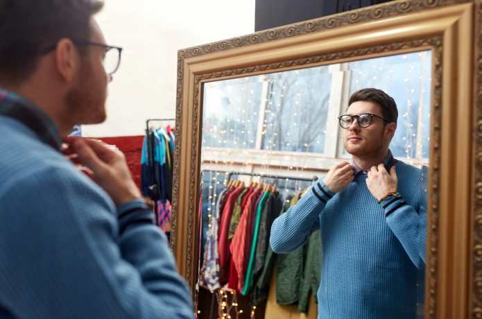 鏡の前で試着する男性の画像