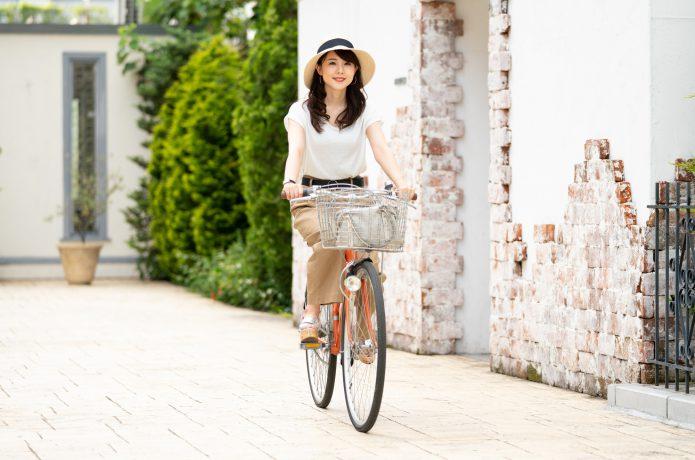 シティサイクルに乗る女性の画像