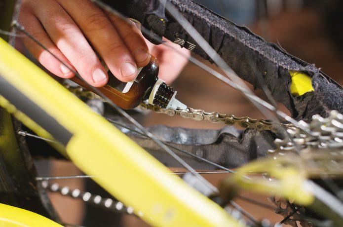 自転車のチェーンにチェーンオイルをさしている画像