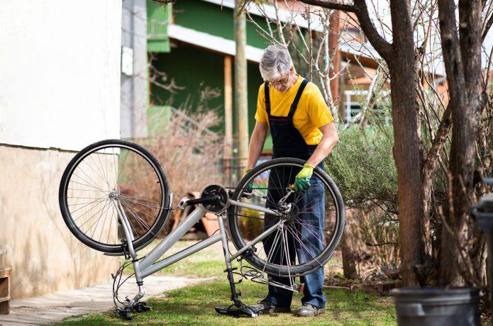 自転車のメンテナンスを行っている男性の画像