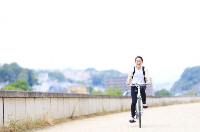 ロードバイクに乗る笑顔の女性の画像