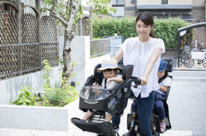 子どもと電動アシスト式自転車に乗る女性の画像