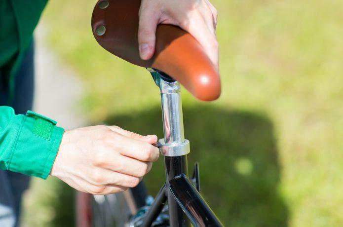 自転車のサドルを調節している人